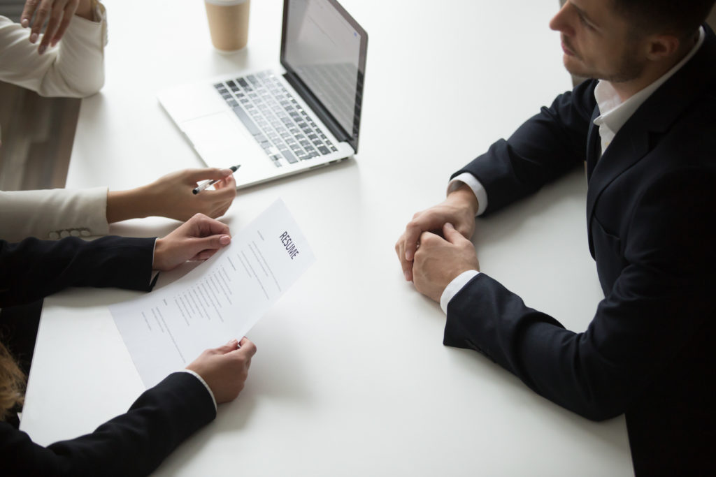 Male applicant having job interview, employers reading resume, asking question. HR representatives hiring young business professional. Recruiting, cooperation, introduction concept. Close up top view