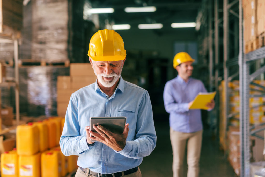 Senior adult bearded businessman with helmet on head using tablet while standing in warehouse. In background his younger colleague holding folder.