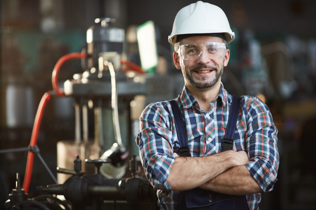Waist up portrait of mature factory worker wearing hardhat looking at camera while standing in workshop, copy space