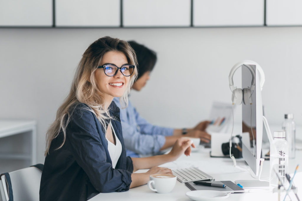 Attractive laughing freelancer girl posing with cup of coffee at her workplace. Chinese student in blue shirt works with document in campus with blonde friend in glasses.