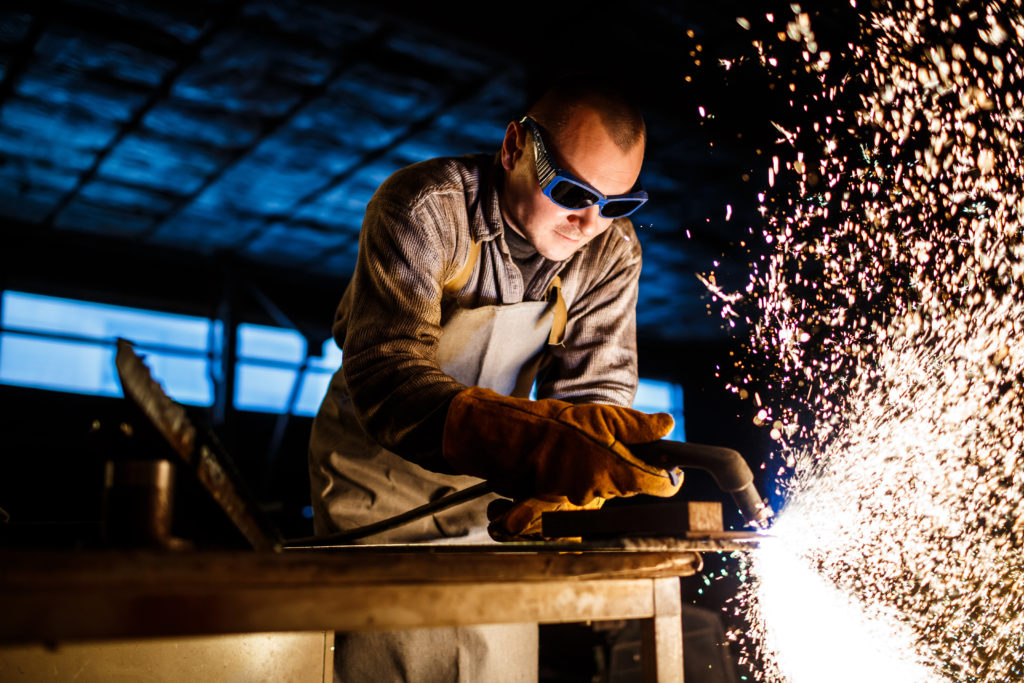 Worker cutting metal with plasma equipment on plant.