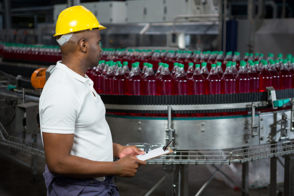 Side view of male worker inspecting bottles in juice factory