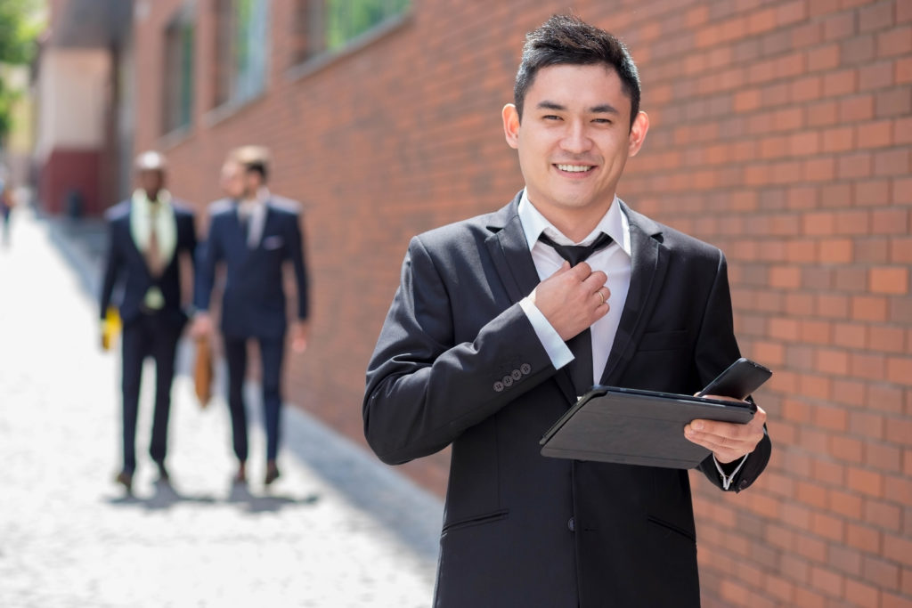 Portrait of multi ethnic business team. Three happy smiling men standing against the backdrop of the city. The foreground of a Chinese man with phone and laptop