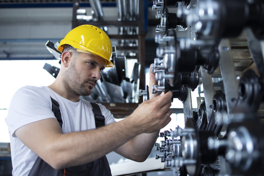 Industrial worker working at production line in factory.