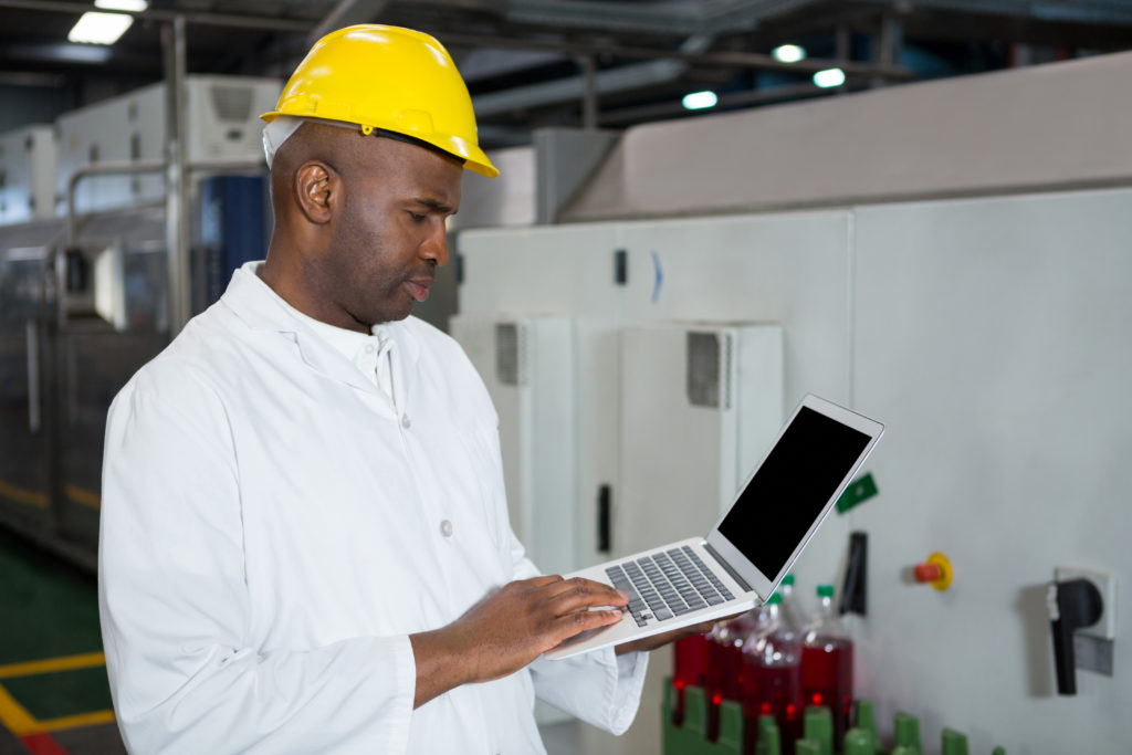 Serious male worker using laptop in juice factory
