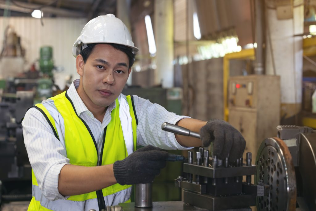 A worker in glasses standing near industrial equipment and verifies production. man operating machine in the factory