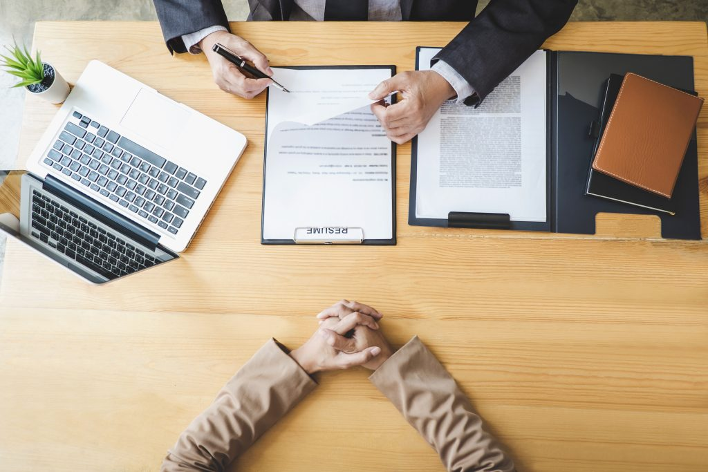 Interviewer or Board reading a resume during a job interview, Employer interviewing a young female job seeker for recruitment talking in modern office, employment and recruitment concept.