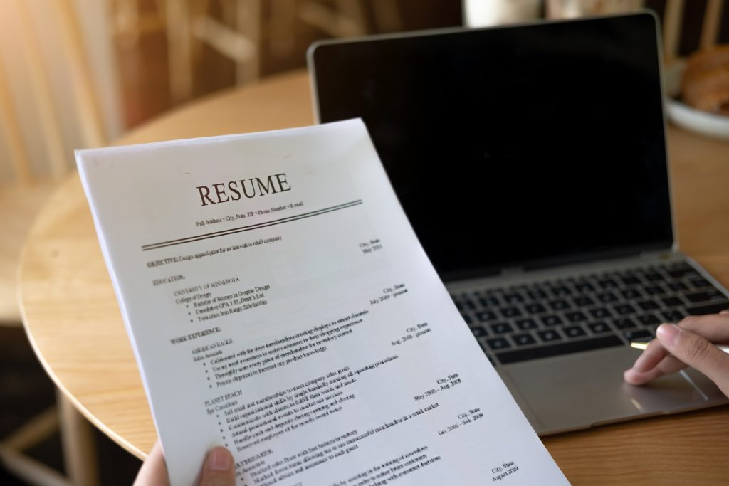 Businesswoman or job seeker review his resume in coffee shop before send to finding a new job with pen and laptop, Business people concept.