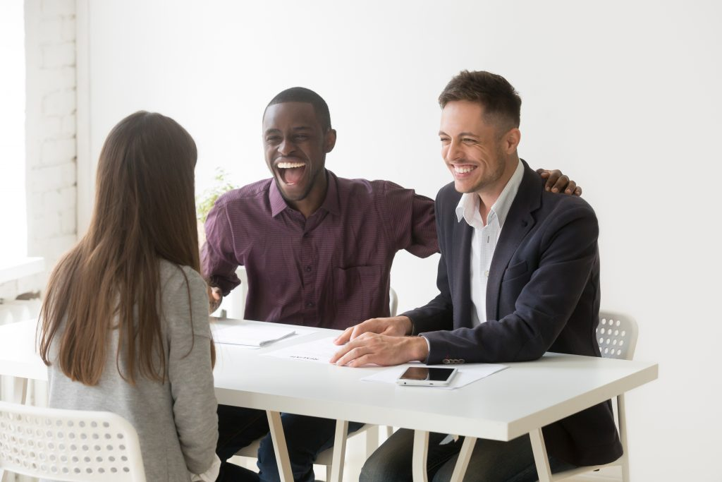 Multiracial hr managers laughing at funny humor joke during job interview talking to woman applicant, candidate makes good first impression at excited african and caucasian recruiters, hiring concept