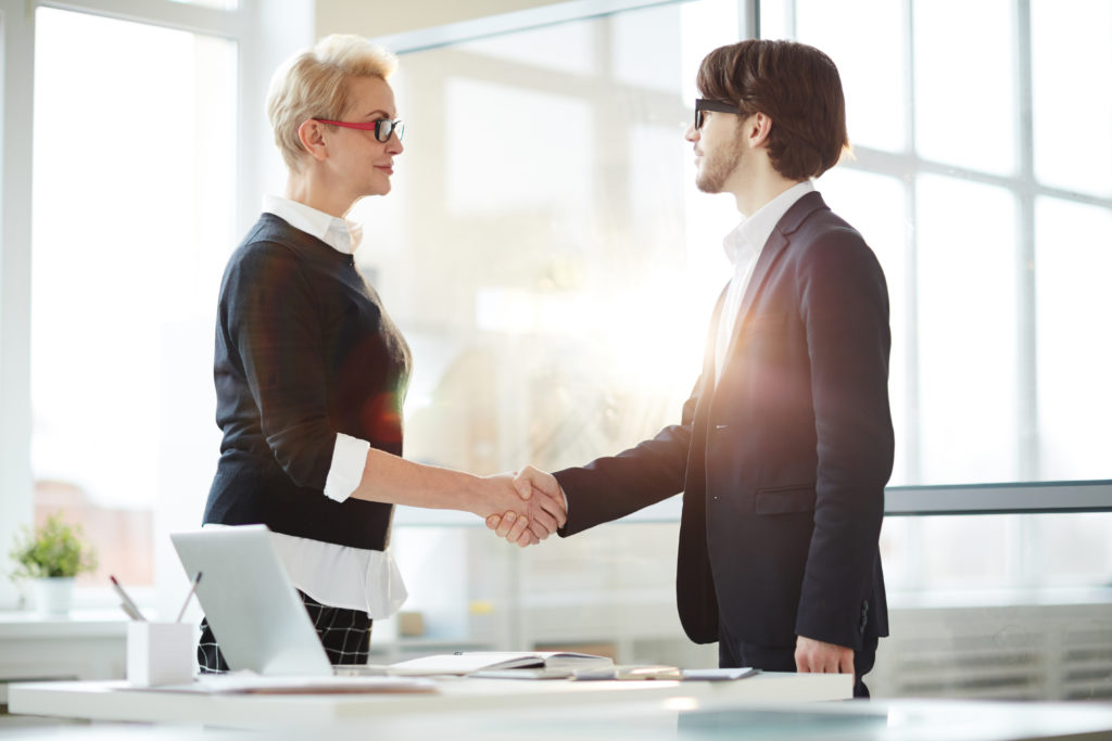 Mature businesswoman and young entrepreneur shaking hands after successful negotiation