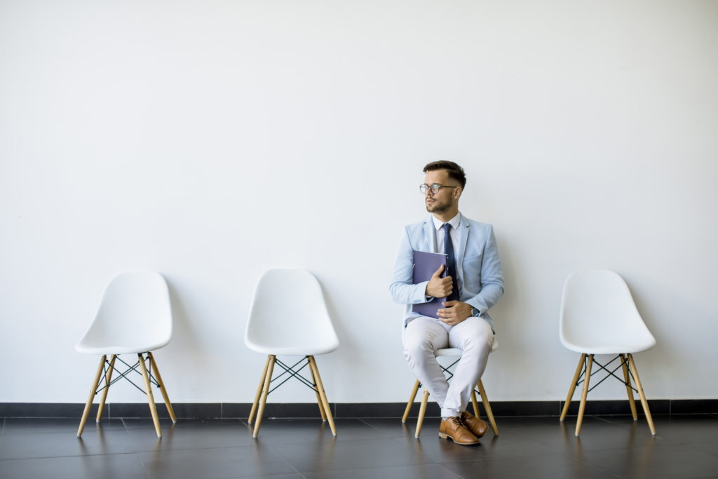 Young man sitting at chair in the waiting room with a folder in hand before an interview