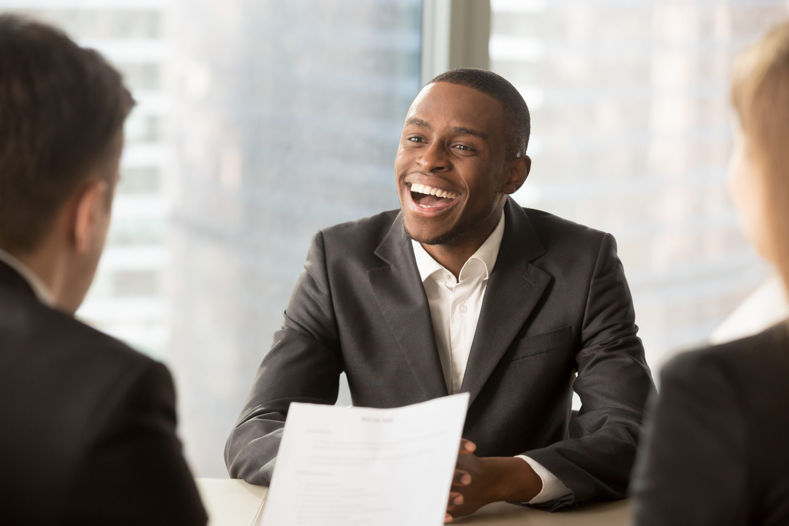Happy black successful candidate getting hired, cheerful african applicant with beaming smile got a dream job in big company, dark-skinned businessman excited by great news